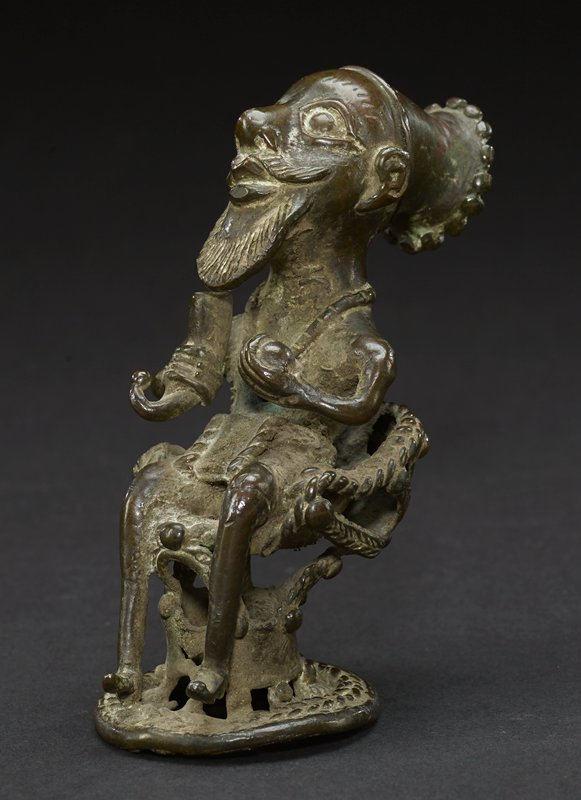 figurative, brass staff finial with small, seated man holding an object in each hand; figure's head is tilted up and adorned with a cylindrical headdress extending away from him; the top of the headdress is flat with a beaded pattern at the rim; figure's eyes are large, with round pupils at center; he has a mustache that curves up at the ends and a round beard; the figure wears a necklace and a square cloth around his waist, which covers his groin; the chair in which the figure sits is complex in design, with beaded and braided patterns and cutouts, and a flat, round base with beaded and braided accents; figure's legs point out in front of him and his feet do not reach the ground