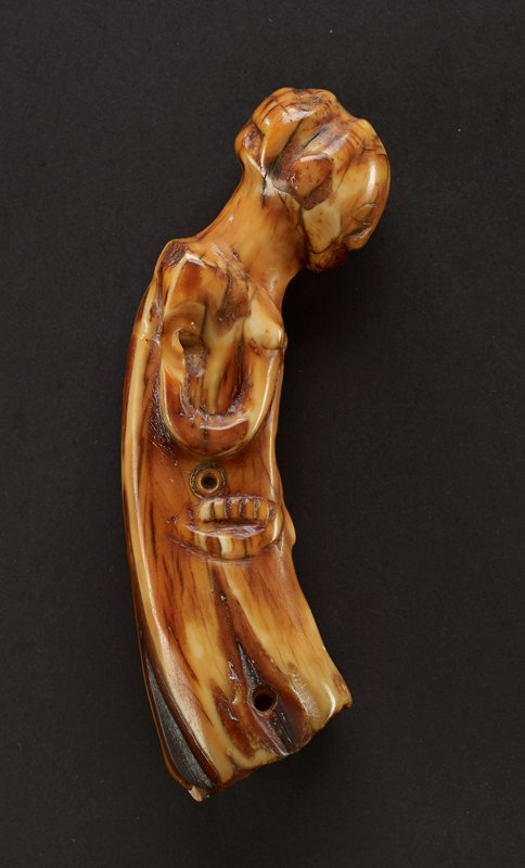 amulet of a bending female figure cylindrical in shape with a round, bumpy top; directly beneath the round top the wood curves in, and then connects to the larger base; face of figure is distinguished with shallowly carved eyes, mouth, and nose; her arms bend upward toward two small bumps resembling breasts; main body of amulet has various carvings, with holes possibly resembling eyes, and semicircular carvings, similar to a mouth; bottom of piece is flat; entire piece is made of hippo ivory and has alternating darker and lighter shade of the natural material