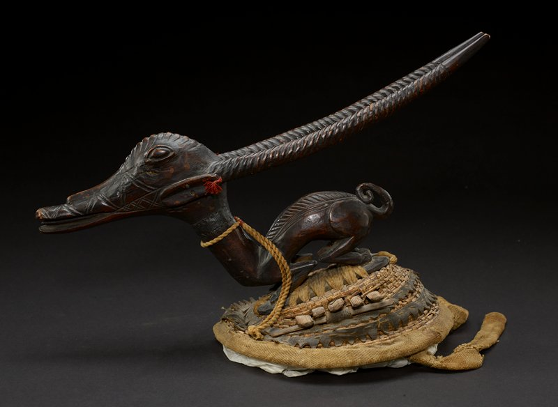 one of a pair of dance headpieces adorned with a small wooden figure of an antelope; figure rests on top of woven basket; antelope has long snout with an open mouth and slightly protruding tongue; its eyes are almond shaped and positioned on the upper side of either side of the head; its ears are oval and situated on either side of the head, each with a red loop tied through it like an earring; the animal's head and back are decorated with carvings; long antlers are carved in spiral patterns and protrude out away from the figure; a long, thick neck connects to the round but lithe body of the antelope; the animals rests back on its haunches and has a rope tied around its neck; a metal band is also present at the animal's neck; the figure sits on a woven mound that resembles an upside down basket; the entire body of the antelope is the dark brown of the wood from which it is carved