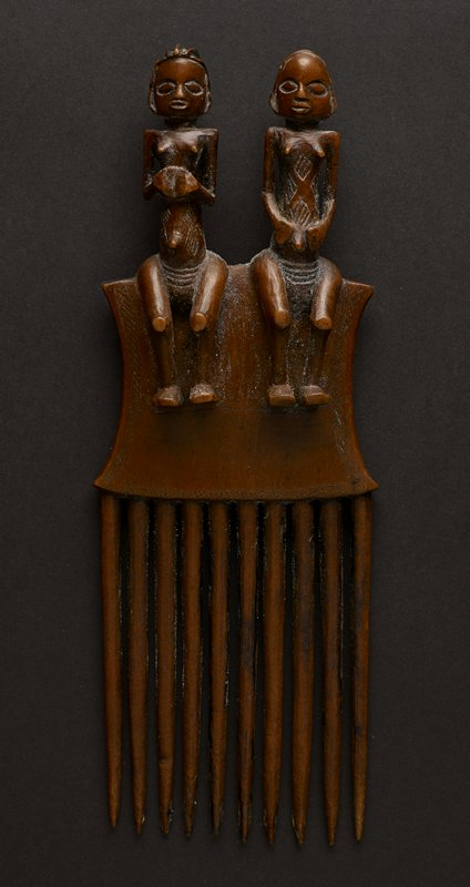 comb with two figures perched atop a square base with concave sides and patterning; ten pointed teeth attached at bottom of base; figure on left has a round head with vertical rows of hair; eyes are oval and mouth is small and partially open; the left figure's shoulders are pointed, with arms at side and hands resting on upper torso; figure has protruding breasts and belly button; the torso is decorated with four diamond-shaped carvings; the figure's hips are wide-se; the figure's knees protrude out into space with legs and feet resting against the base of the comb; the figure on the right has similar features, but hair is represented by horizontal rows, arms are less rigidly bent and thus hands rest easily on lower belly; the figure on the right also has torso decorated with diamond-shaped carvings; from behind the figures' buttocks are visible at top of base; entire piece is the reddish tan hue of the wood