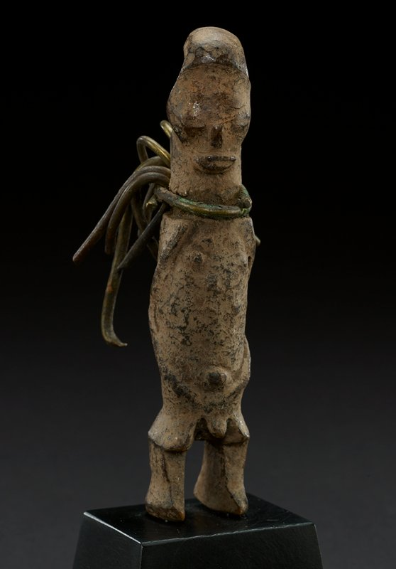 figure is human male; round headdress at top of head; forehead is slightly misshapen; details of the face are worn, but there are wide eyes, small nose and smiling mouth; neck is undefined; body continues from the head; small detailing of nipples and belly button on torso; small penis; legs are slightly bent at the knee with unpronounced feet at the bottom; metal cord wrapped around neck and continues at the back of the figure; natural color with heavy wear