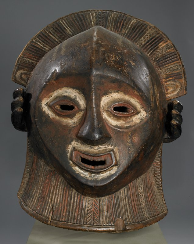 Dance Mask; Carved in the round from a single piece of lightweight wood. Interior hollow. Features remarkable in that they resemble Greek and Sicilian works of the 6th Century B.C. The back of the mask, carved in terrace and striated patterns, contrasts with the smooth lateral contours of the face.