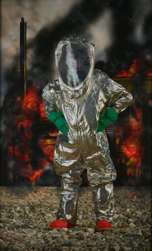 standing figure with hands on hips, wearing a shiny silver HAZMAT suit, with green gloves and orange shoes; figure stands on gravel, with flames behind