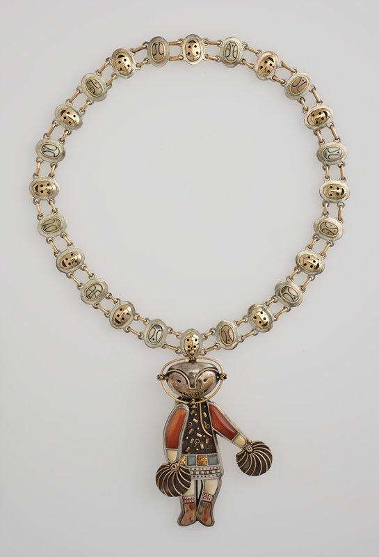 pendant: standing figure holding pompon-like elements; silver mask with wide smiling mouth with visible teeth lifts to reveal a fossilized ivory face with mouth in an O shape; PR arm is hinged; element in PL hand is movable; figure wears skirt with alternating brown and white veined and grey stones, bordered with ivory band with black vertical and horizontal lines and red dots; figure wears green, tan and brown mottled boots; pin on back; necklace: alternating oval elements--gold flatter mask-like element with incised designs alternate with raised inset ivory elements with black designs