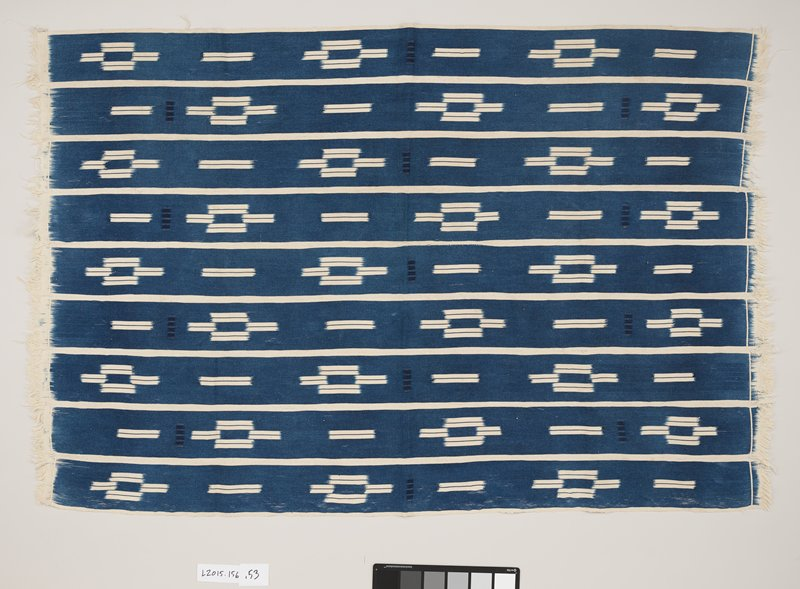 blue and cream rectangle-shaped panel; cream fringed edges on two shorter sides; nine strips of fabric stitched together to form panel; each strip of fabric has a blue background with cream horizontal lines forming a diamond shape, framed by cream edging lining each strip; four darker blue squares added throughout design
