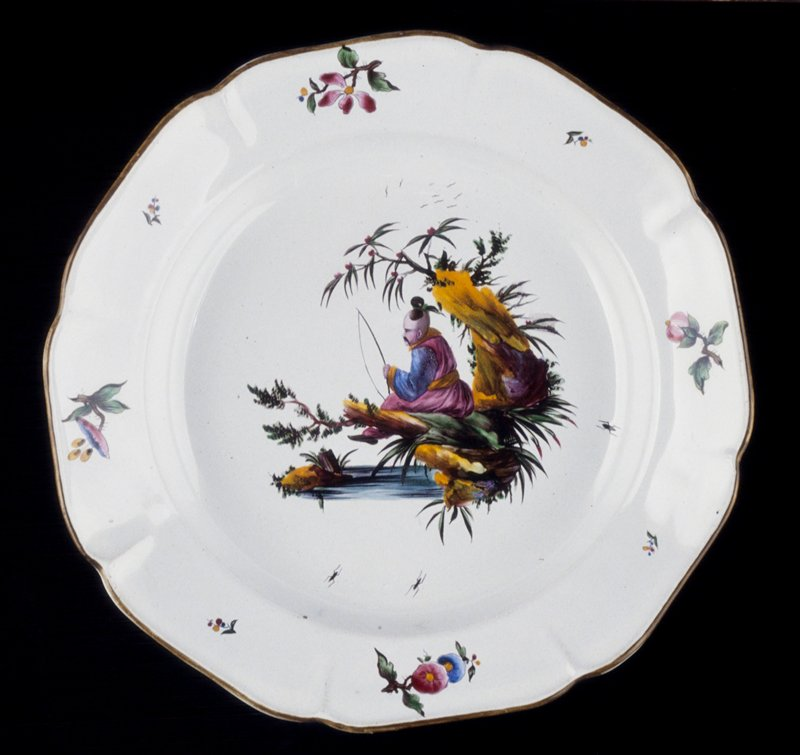 faience soup plate of lobed octagonal shape; rim edged with green-brown glaze; chinoiserie scene in center; edge of plate is completed with the application of small sprays of flowers of the indianische blumen type; reverse shows double set of stilt marks, typical of petit feu wares