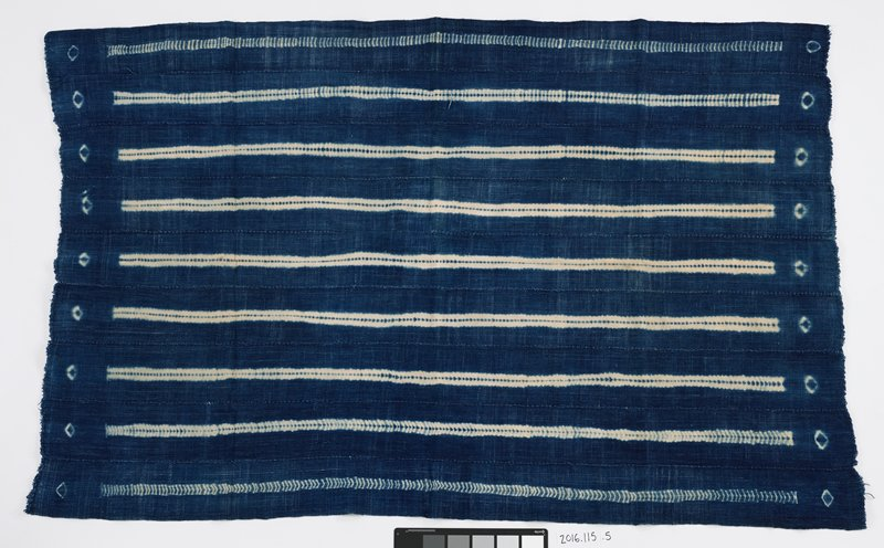 nine strips of fabric stitched together to form panel; blue dyed background with nine white stripes running length-wise; white stripes are divided by thing blue stripe; white ringed ovals edge stripes