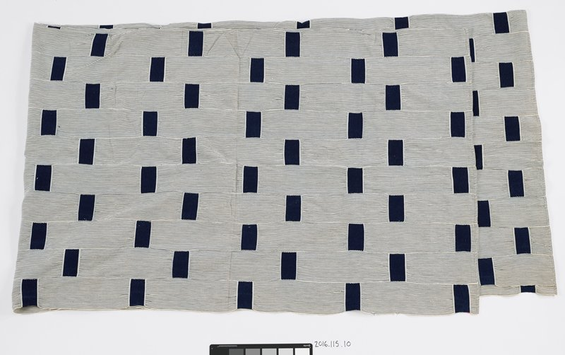 white cloth with thin, dark blue strips; dark blue woven rectangles overlap; twenty strips of fabric stitched together to form panel