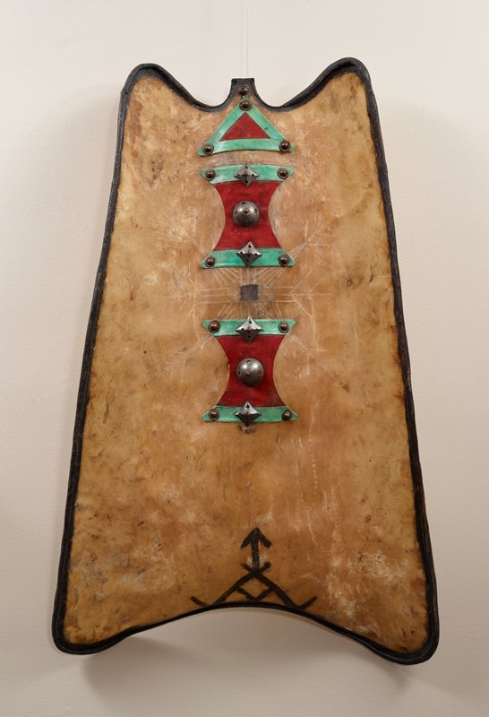 roughly rectangular shaped with rounded edges, with long sides tapering slightly toward top; inward curve at bottom edge; two looping curved at top; rounded surface with concave and convex areas; body is light-colored hardened animal hide, with curled-over, darkened edges; three decorative elements with green hide trim, red cloth and metal ornaments (large domed metal studs in two sizes and four pyramidal metal elements)--two roughly hourglass-shaped elements and one triangular element; some incised lines forming a starburst at center; arrow and lines in dark pigment at bottom center; metal handle on back; handle covered in dark brown leather