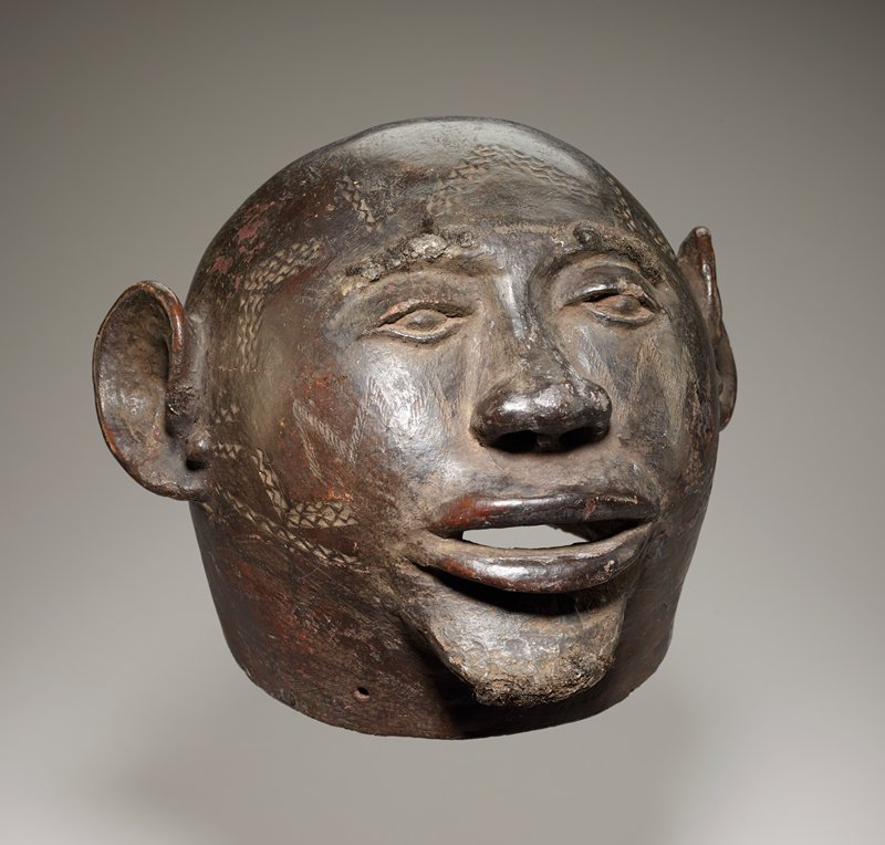 rounded head with thin coat of dark slip; friendly features with eyes mostly open, broad nose, wide open, smiling mouth, and prominent chin; eyebrows and chin adorned with human hair attached with wax; holes around base of neck