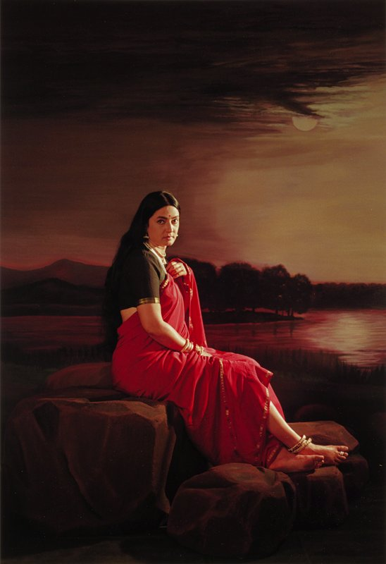 profile portrait of a woman in red sari seated on rocks; painted backdrop of moonlight scene over calm water and trees