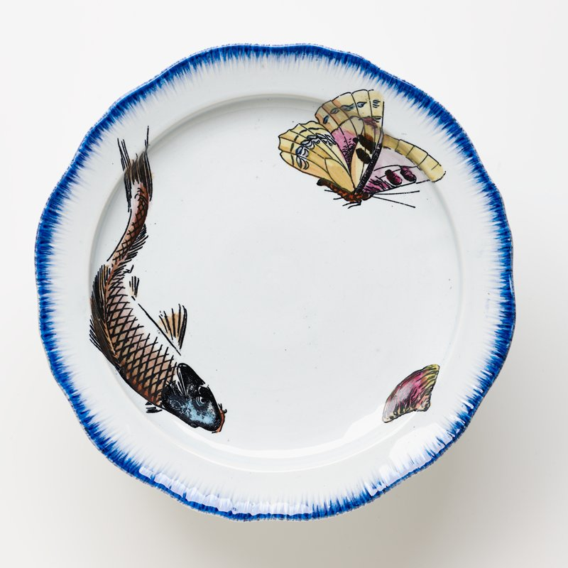 cake plate with white ground and brushed blue pigment around edge of plate and foot with painted carp with blue head, yellow butterfly and a clam on plate surface and a red flower, lavender butterfly and yellow clams on foot