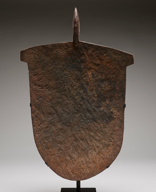 "flat, bell-shaped piece of iron with 7"" prong extending from flat end; irregular surface that primarily rust in color with darkening in center; slight convex curve in overall shape"
