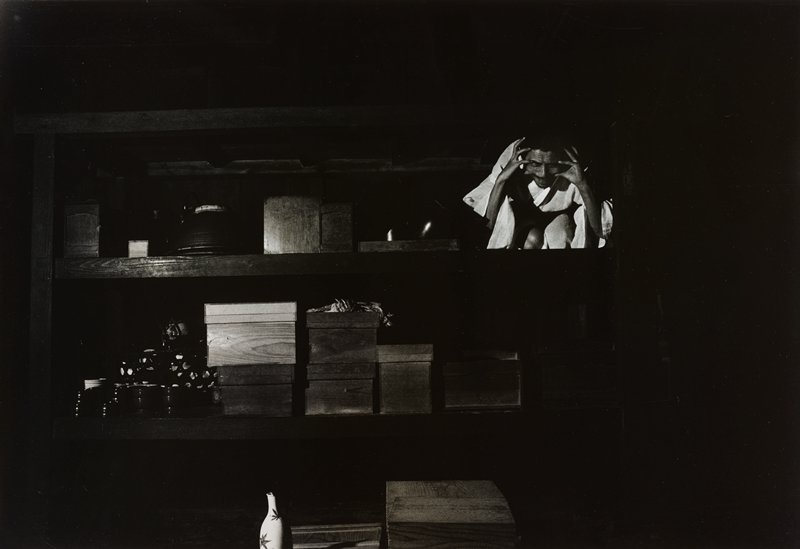 dark scene with rows on wooden boxes on shelves and vase with foliage pattern and bottom, LLQ; squatting man wearing a light-colored kimono, with his fingers splayed, touching either side of his head, in URQ
