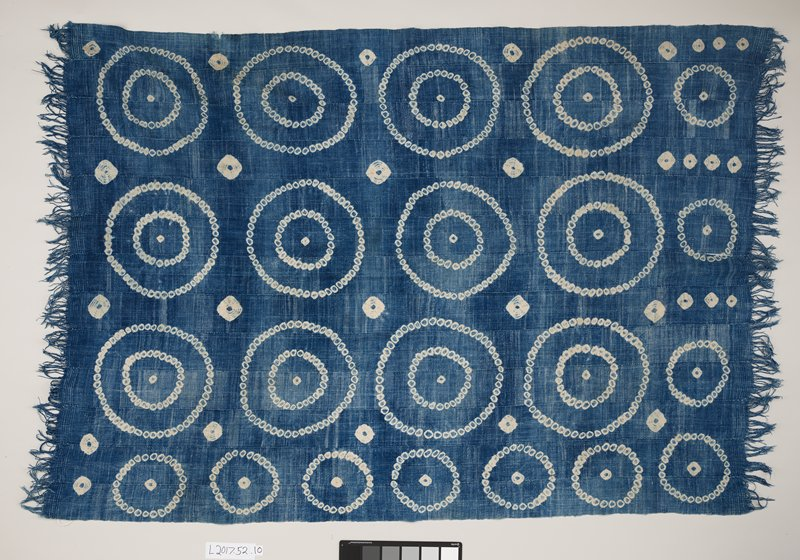 woven strips sewn together; medium indigo with tie dyed designs--rows of concentric circles separated by round forms with spoke-like elements; fringe on short ends