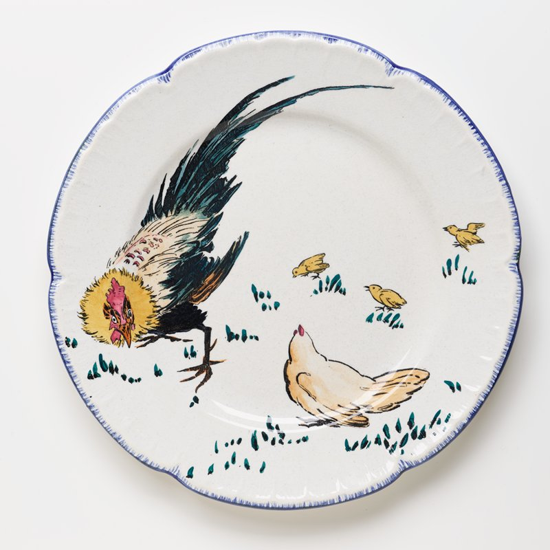 small dinner plate decorated with yellow, green, black, and tan rooster at left, tan hen at bottom center, and three yellow chicks at right; blue scalloped edge
