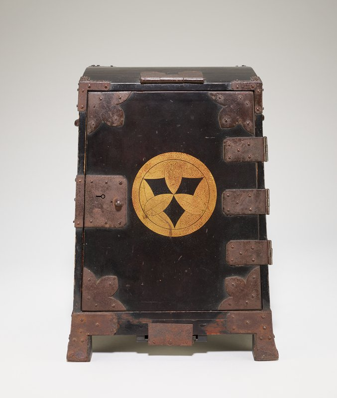 small rectangular chest with flared base to be worn as a backpack; black lacquer with gold round crest on front featuring three rounded leaves against black triangle pattern; 8 drawers inside of varying shapes that fit the irregular shape of the box; navy blue, rough silk cord laced through back