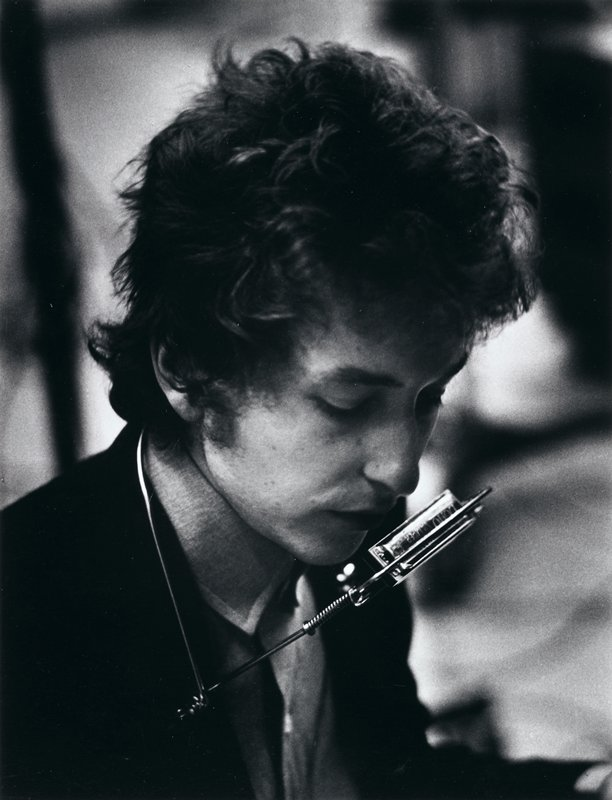 portrait of Bob Dylan, looking down; 3/4 profile from PR; harmonica holder around his neck