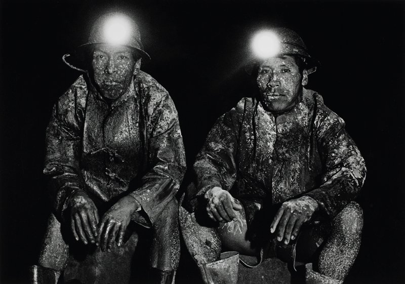 2 seated men wearing hardhats with miner's lights and jackets, with their faces, hands, legs and clothing speckled with white liquid