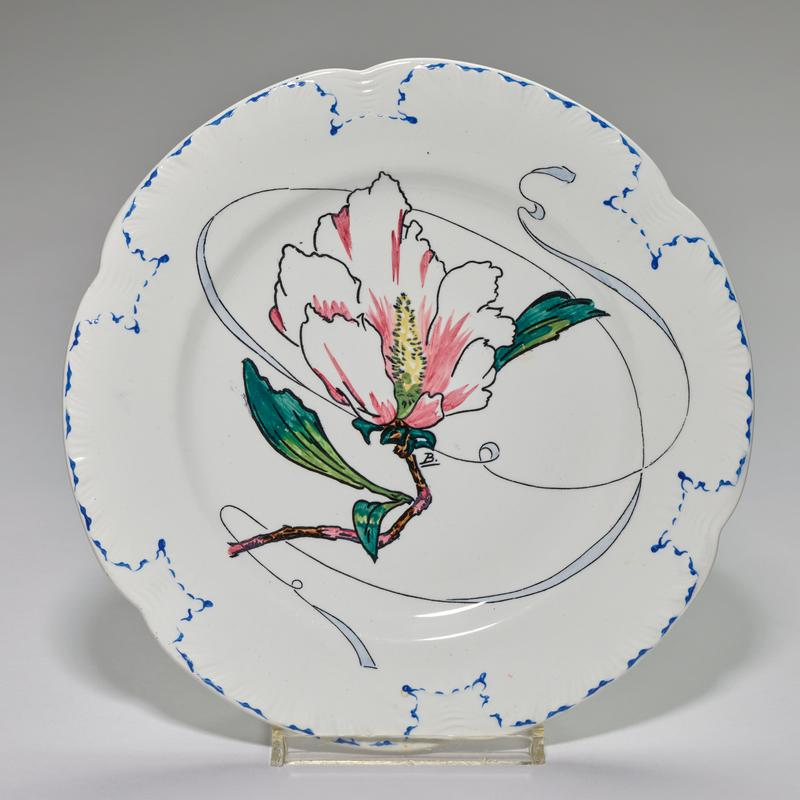 scalloped edge; faience design of large central pink flower with scroll behind; edged in blue pattern