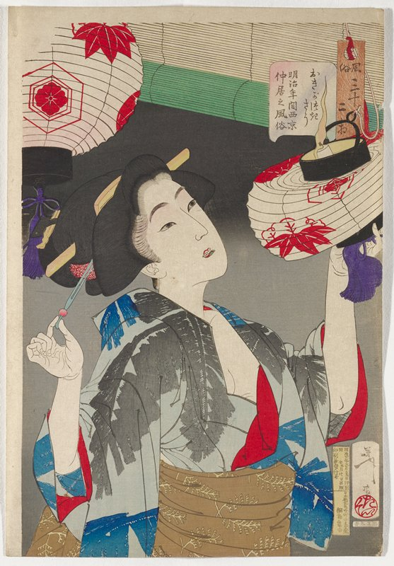 woman collapsing a hanging paper lantern with a burning candle inside; two lanterns visible, which are white with red floral and leaf designs; woman wears a blue kimono with blue and grey abstract leaf patterns, red trim and brown obi with yellow leaf fronds