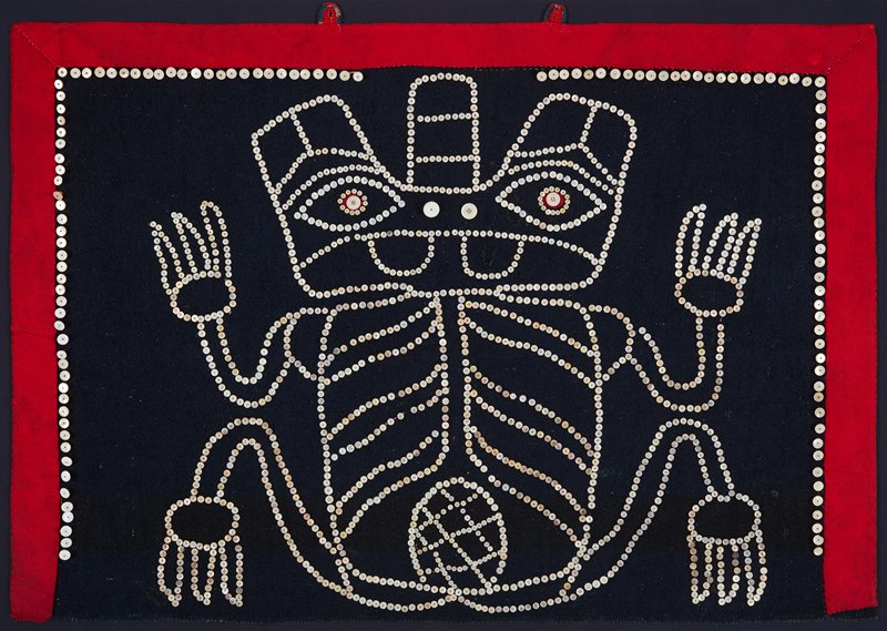 stylized frog-like figure outlined in buttons against navy blue background; red border; figure has three-pronged head, and is seated upright, with arms to side, displaying its belly; stylized ribcage pattern and embellished stomach decoration; in plexi shadowbox