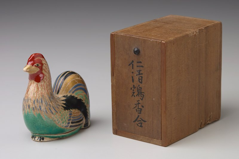 seated rooster, with feathers in red, black, green and blue glaze and gilt; has storage box