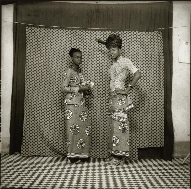 two standing women, facing each other, with heads turned to face picture plane; shorter woman at left holds a small bouquet of flowers; taller woman at right has her PL hand on her hip and wears a headwrap and a lace blouse; blouse and skirt of woman on left and skirt of woman on right are the same circle-patterned fabric; dotted curtain behind women; checked tile floor
