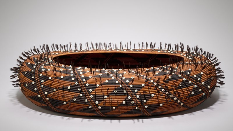 large squat, oval basket with small, erect black-brown feathers; diagonal woven decorations in black, of double triangles, and lines with small checks; white buttons with red or blue beads stitched into black details