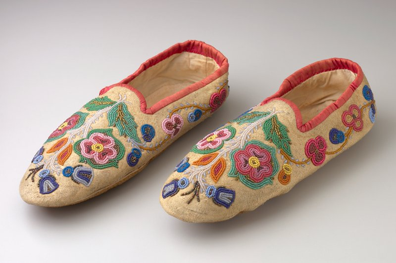 slipper-style without fasteners; floral motif beadwork on tops and sides in multicolored and metallic beads; red cloth around foot openings; lined with white cloth