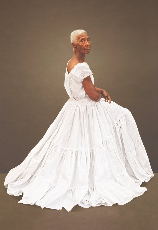 thin elderly dark-skinned woman with short white hair, wearing a long white dress with three gathered tiers, seated, looking over her PR shoulder; grey-brown ground; received framed and unglazed in black poster frame