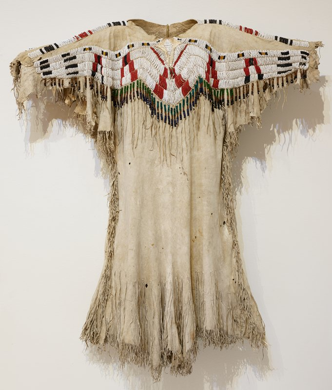light tan hide; beaded bodice on front and back with black, white, red, and yellow beads in arcing horizontal rows on front and back, and band of beads on top of each sleeve; hide fringe below bands of beads with larger blue, brown, black, red, and green beads; hide fringe at bottom hem, sides, beneath sleeves, and on sleeve openings