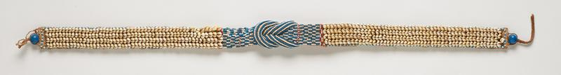central beaded section with predominately blue and white beads, accented with red, in the form of two braid-like loops, stripes of beadwork on the loops and alternating short rows of blue and white beads on either side of loops; long sections on either end of rows of cowrie shells edges with larger blue and white beads; large blue bead at each end; tan cloth backing