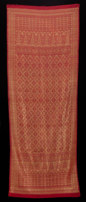 red fabric with gold thread; red borders along short edges; gold embroidery throughout in abstract geometric design; gold stripes along long edges; gold bands with circles along long edges; bands with floral design and triangles pointed toward short edges; six-spoke wheel/star motif in bands; bird motif next to spoke-style stars (?); diamond and six- and eight-point stars with geometric and spiral decoration throughout; short folded and stitched seams along short edges