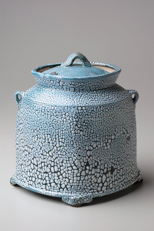 heavy lidded jar with 4 small feet; rounded rectangular shape with slanted shoulder; square lid; 2 small decorative handles at opposite corners; small pulled handle on lid; dark blue glaze overall with mosaic-like white tessura on top