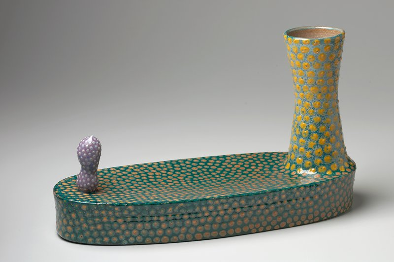 ovoid base with flat, slightly flaring sides and concave top; vertical element with 2 lobes at one end; tapering and flaring base at other end; base and vase covered with green glaze and yellow spots; lobed element is purple with white spots