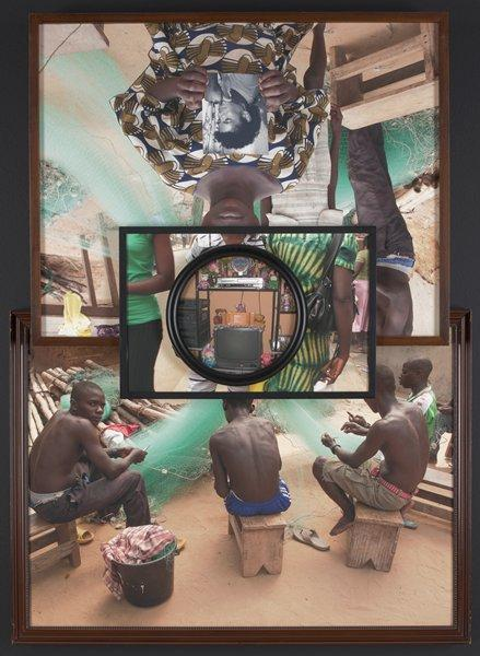 four separate colored photographs layered over each other and attached with black tape on the back; bottom photograph depicts four boys, seated, weaving a fishing net; boy on left turns to look at viewer; brown frame with beaded inner edging; top photograph image of figure in a patterned dress, holding a black and white portrait with both hands; face is obstructed by another photograph layered on top of the image; two figures stand behind front figure, with cascading fishing nets in the background; brown frame; center photograph depicts the torsos of three figures, right figure wearing a green and yellow tie dyed dress, holding a black purse; center figure wearing a white striped patterned button up shirt with matching pants; left figure wearing a green cotton shirt with black bottoms; image obstructed by center photograph overlapping; center photograph is round in shape, with an interior view of a televisions surrounded by electronic equipment on shelving; stuffed bears rest on shelves around television; rectangular gold trophy/ award rests on top of the television; cleat taped to back of installation