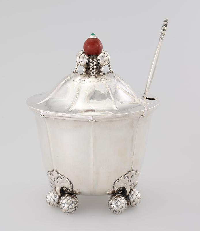 silver tureen with vertical lines on the body of the tureen and move upwards onto the lid; amber colored rounded handle with green tip on top of lid, nestled in curving four curving leaves that alternate with four bunches of small berries; legs of tureen are acorns, grouped in pairs; inner lining with round inner ring inside tureen