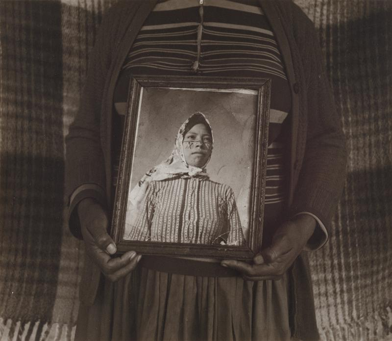 torso and arms of a woman wearing a sweater, skirt, and shirt with horizontal stripes of various widths, in front of a plaid fabric panel, holding a framed photograph of a young woman wearing a headscarf and vertically striped blouse, with a horizontal line across her cheeks and nose and geometric designs on her cheeks