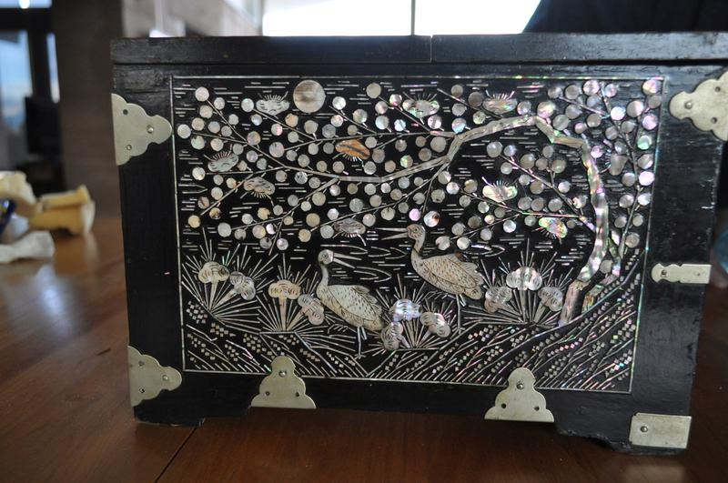 box with two removable drawers and top with two pairs of hinges containing a mirror; inlaid mother-of-pearl designs; two cranes on top with branches with fruit; front of drawers have hexagonal pattern with starbursts; right decorated with deer in a landscape with trees; left decorated with cranes in a landscape with trees; plants on back; lock and key included