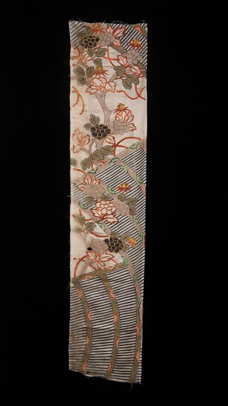 silk panel; tree in orange silk applique at top center; scattered blue flowers with gold threading that outlines flowers; sections of blue and white striped curving areas at bottom, in center and at top corners