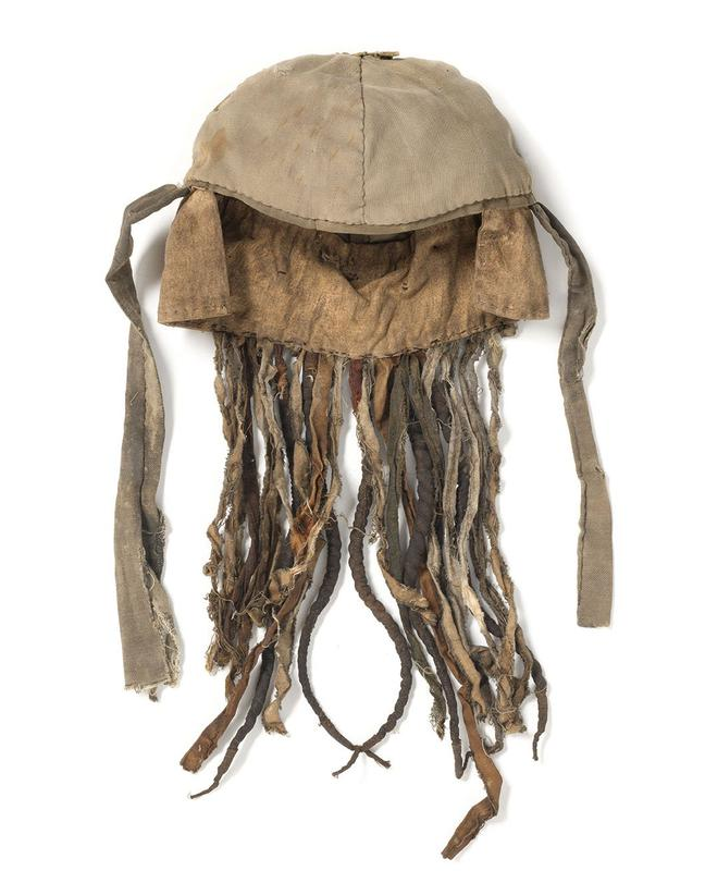 headdress, with tan cloth cap and small brim; metal bells and other metal strips attached to banding; cloth cords and strips of cloth fabric hang at base