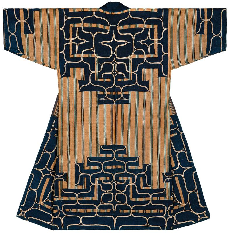 wheat-colored background with bands of vertical blue, off-white, and indigo stripes; indigo applique around lower half and ends of sleeves with organic meandering embroidery, with off-white and orange couching