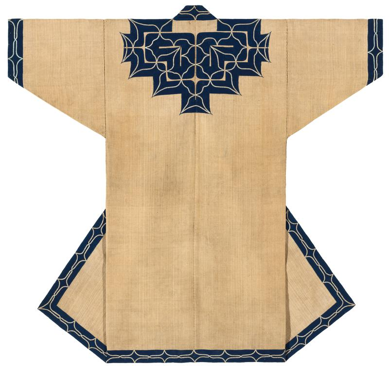 tan robe covered with navy blue applique trim on sleeve cuffs, collar and yoke, center back, and along center edged and bottom trim; off white embroidery over navy applique creates curving lines and points