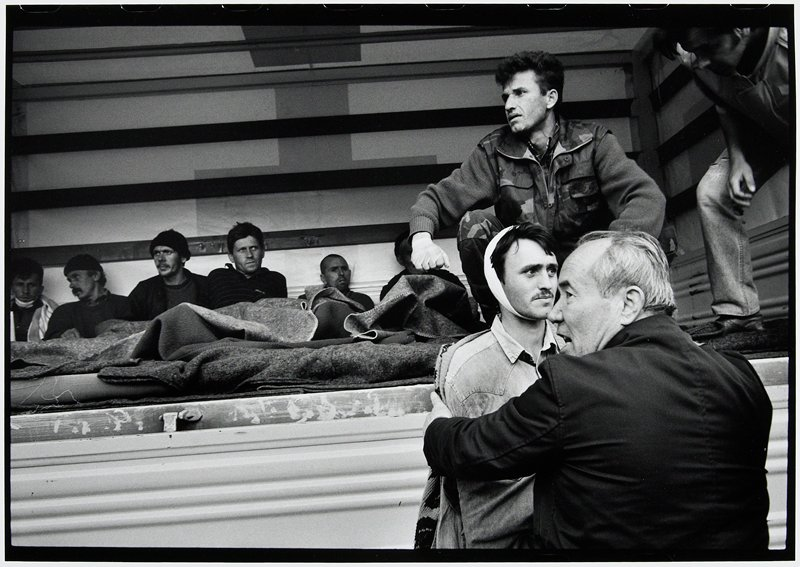 row of men seated in shelter, man in front with bandaged head