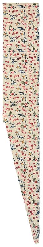trapezoid shaped fragment of white fabric with multicolored pattern throughout; pink, red, and purple blossoms, green leaves, blue leaves and vines, yellow and orange fruits; two finished sides