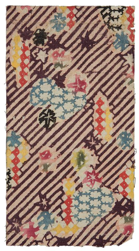 rectangular fragment of purple and pink striped fabric with multi-colored pattern; pattern over diagonal stripe background consists of red, blue, yellow, green, black, and pink stars, diamonds, and leaf shapes