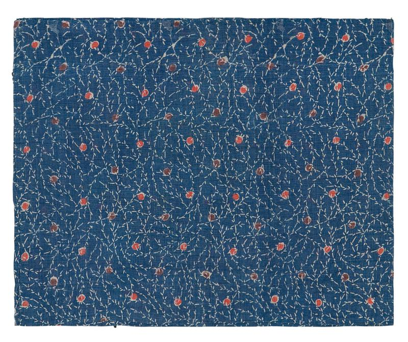 rectangular blue fabric with white vines and alternating lines of red and brown dots; fragment sewn on one side, folded on other; open top and bottom, hemmed edge along bottom