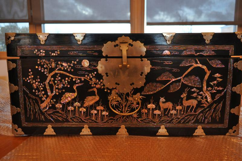 dark brown lacquer with inlaid mother-of-pearl; hinged cover; top has central longevity symbol flanked by two flying cranes and fruits on branches; front has pair of deer on right side and pair of cranes on left in a landscape with trees; left and right ends have fish with trees; back is plain; large floriform metal fitting with latch on front; blue paper at interior; lock included (no key)