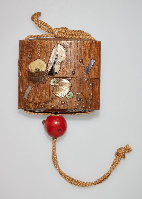 inro with rectangular compartment; rounded form; medium brown patina with branch in relief with various symbols; ojime in the form of a red persimmon with green leaves; tan silk cord
